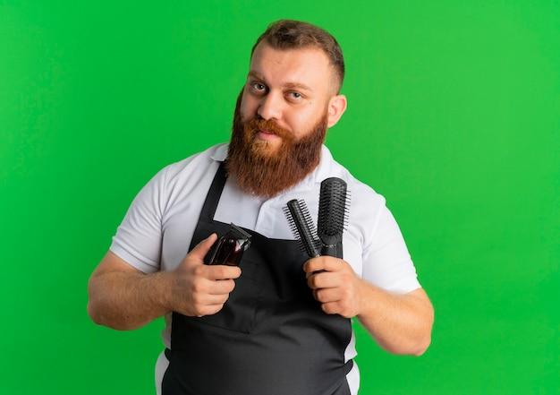 Hombre barbero profesional en delantal con máquina de afeitar y dos cepillos con expresión de confianza de pie sobre la pared verde