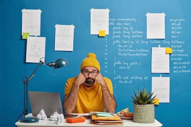 Hombre barbudo aburrido trabaja con un dispositivo portátil y papeles, sostiene las mejillas, mira a la cámara, se prepara para estudiar el seminario