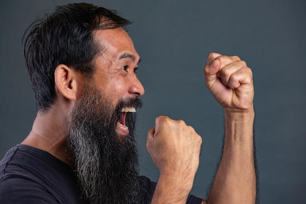 Hombre barbudo actuando ira humor en pared oscura