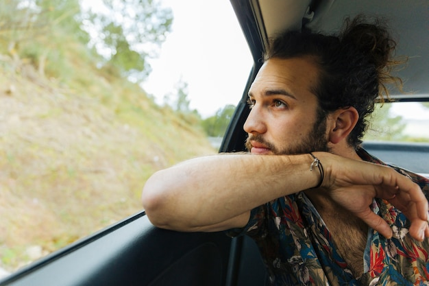 Hombre barbudo admirando vistas desde la ventana del coche