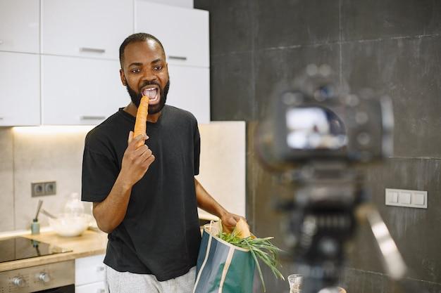 Hombre barbudo afroamericano sonriendo y sosteniendo un paquete con comida