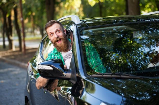 Hombre barbudo alegre en el coche.