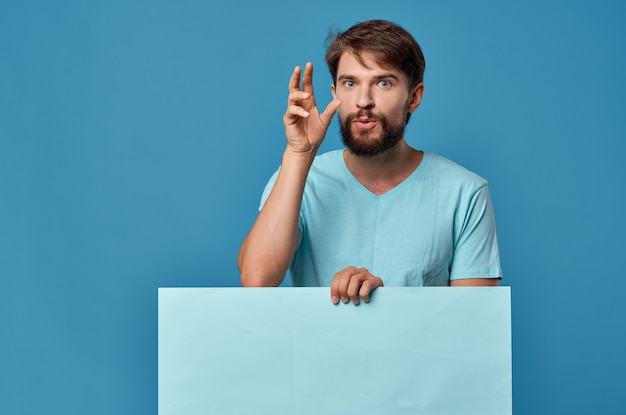 Hombre barbudo alegre en fondo de cartel de maqueta de camiseta azul aislado