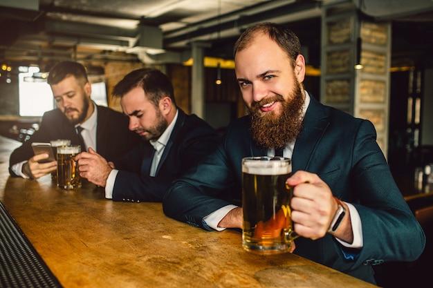 Hombre barbudo alegre y positivo en traje mira en cámara. él sonríe y sostiene la jarra de cerveza. otros dos jóvenes se sientan detrás.