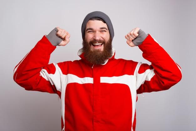 Hombre barbudo alegre en ropa de invierno celebrar