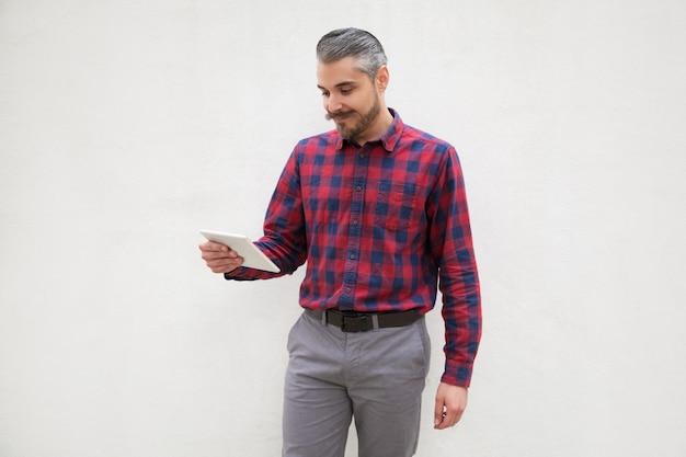 Hombre barbudo alegre con tablet pc