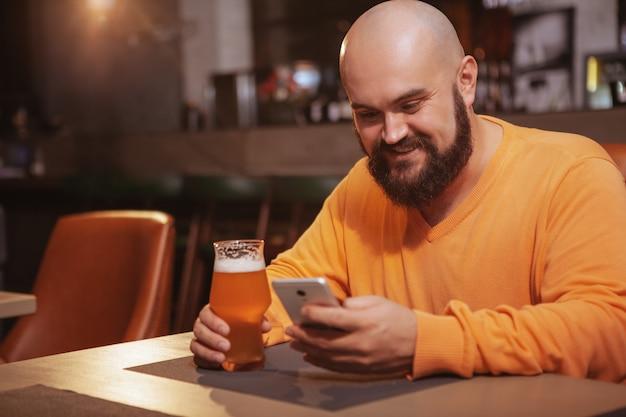 Hombre barbudo alegre usando su teléfono inteligente mientras bebe cerveza en el pub