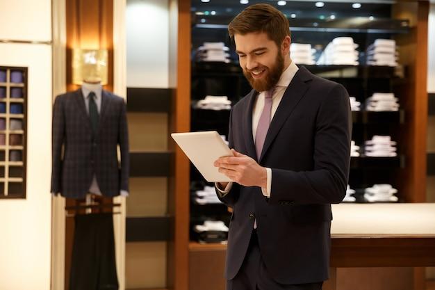 Hombre barbudo alegre usando tableta
