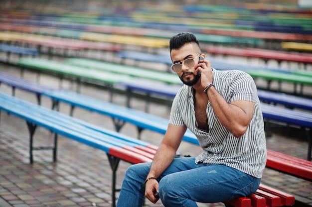 Hombre barbudo alto de moda con camisa, jeans y gafas de sol sentado en una fila de bancos de colores y usar su teléfono