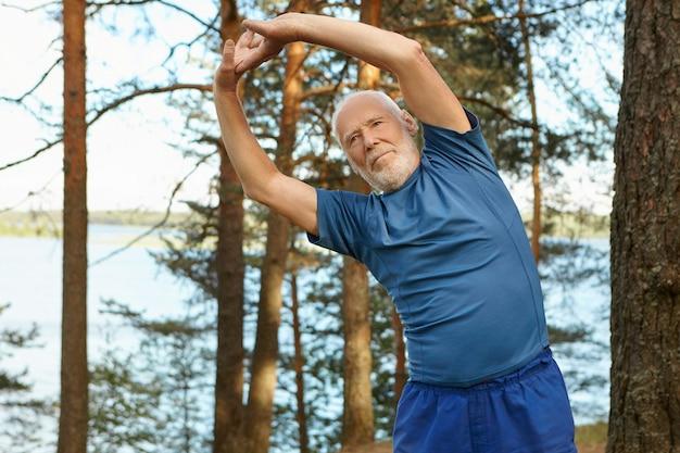 Hombre barbudo anciano autodeterminado enérgico en ropa deportiva posando al aire libre con el bosque y el río, manteniendo los brazos en alto, haciendo curvas laterales, calentando antes de ejecutar el ejercicio