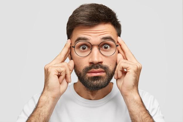 Hombre barbudo asombrado mantiene los dedos índice en las sienes, mira con expresión estupefacta, trata de recordar detalles del robo