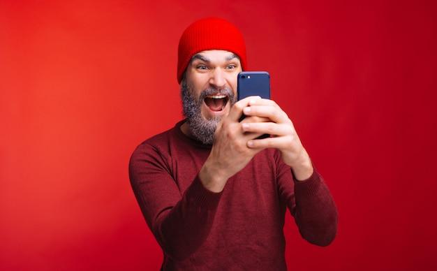 Hombre barbudo asombrado mirando smartphone, tema de invierno