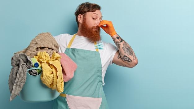 El hombre barbudo astuto cierra la nariz con los dedos por un olor desagradable, recoge toda la ropa sucia, usa una camiseta informal y un delantal con pinzas para la ropa, tiene un tatuaje, se para sobre una pared azul, espacio libre
