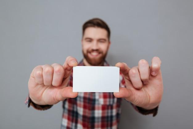 Hombre barbudo atractivo que muestra la tarjeta de visita en blanco