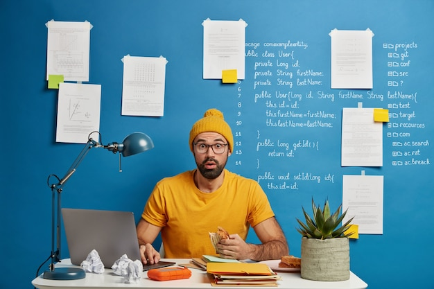 El hombre barbudo avergonzado trabaja en el escritorio, tiene una reacción negativa, come un sándwich, busca información en una computadora portátil moderna, una pila de libros de texto o libretas.