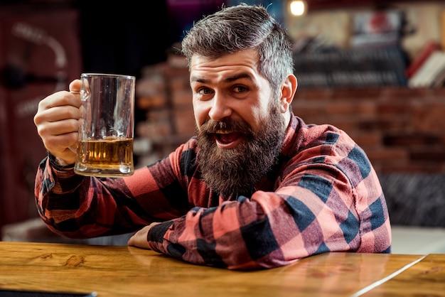 Hombre barbudo bebiendo cerveza en el pub
