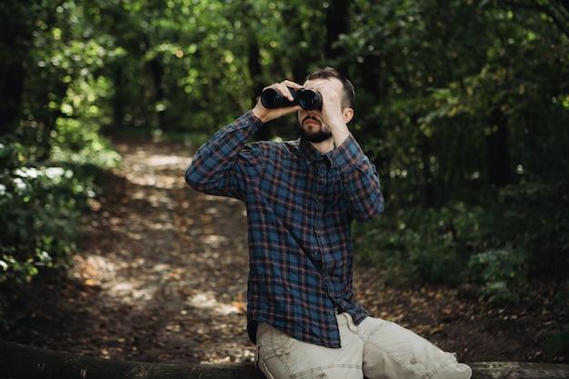 Hombre barbudo con binoculares sentado en la rama