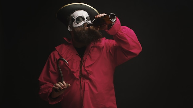 Hombre barbudo borracho disfrazado de pirata con un gancho para halloween sobre fondo negro.