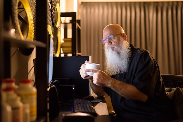 Hombre barbudo calvo maduro bebiendo café mientras videollamadas en el trabajo desde casa a altas horas de la noche