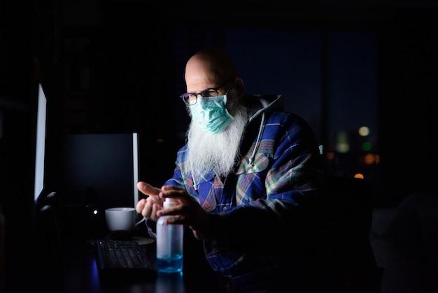 Hombre barbudo calvo maduro con máscara con desinfectante de manos mientras trabaja desde casa en la oscuridad