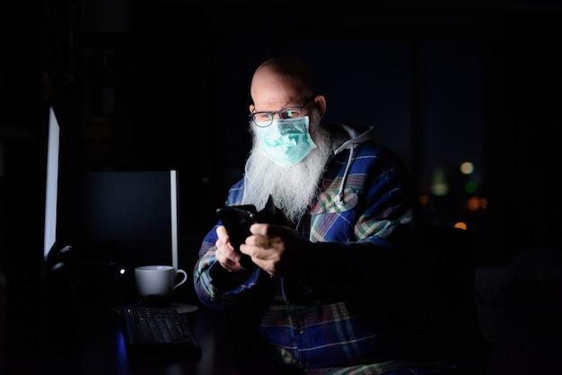 Hombre barbudo calvo maduro con máscara con teléfono mientras trabaja desde casa a altas horas de la noche