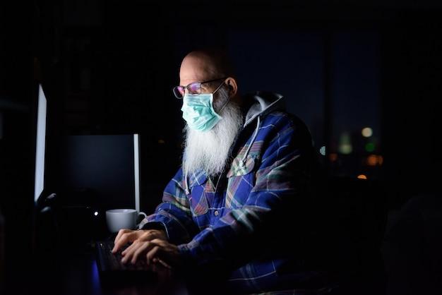 Hombre barbudo calvo maduro con máscara trabajando desde casa en la oscuridad