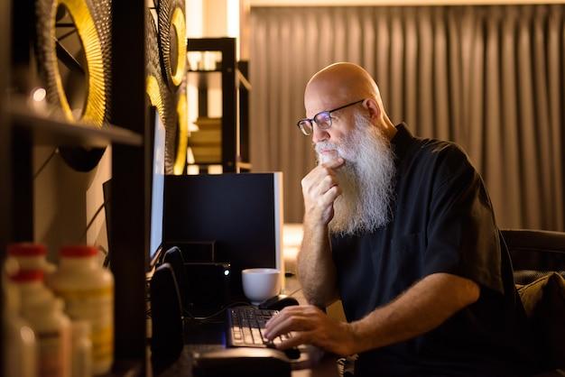 Hombre barbudo calvo maduro pensando mientras trabaja horas extras en casa por la noche