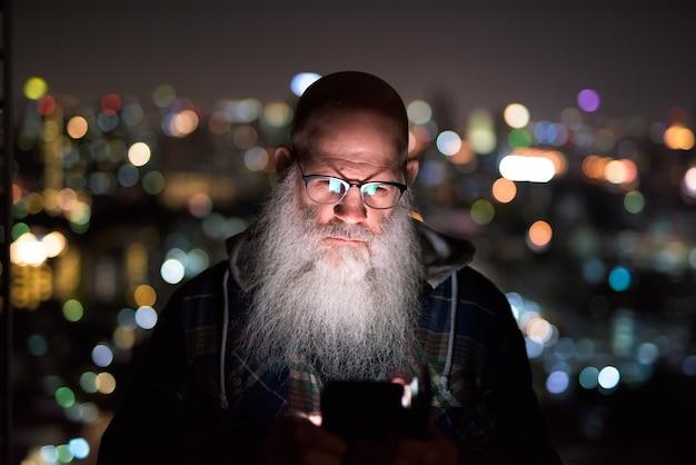 Hombre barbudo calvo maduro con teléfono en vista de la ciudad por la noche