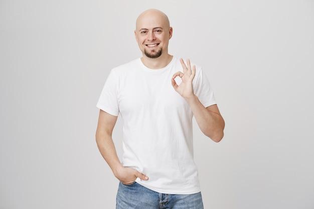 Hombre barbudo calvo satisfecho en camiseta blanca muestra bien firmar, aprobar
