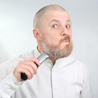 Hombre barbudo con una camisa de color claro hace que el recortador de barba de corrección