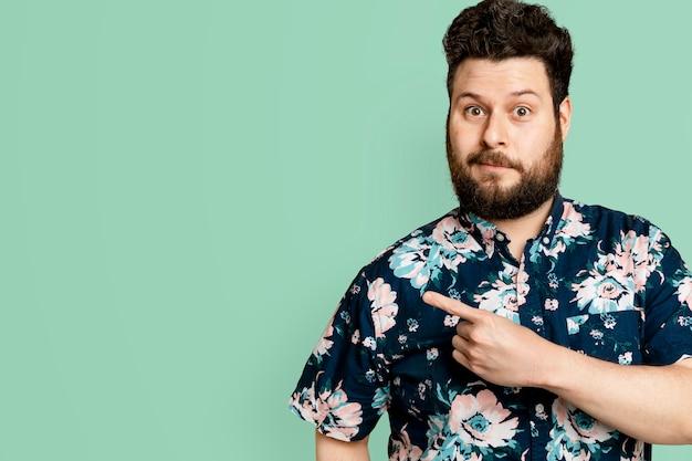Hombre barbudo en camisa de verano floral apuntando hacia el lado