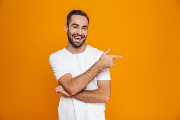 Hombre barbudo en camiseta apuntando con el dedo a un lado mientras está de pie, aislado en amarillo
