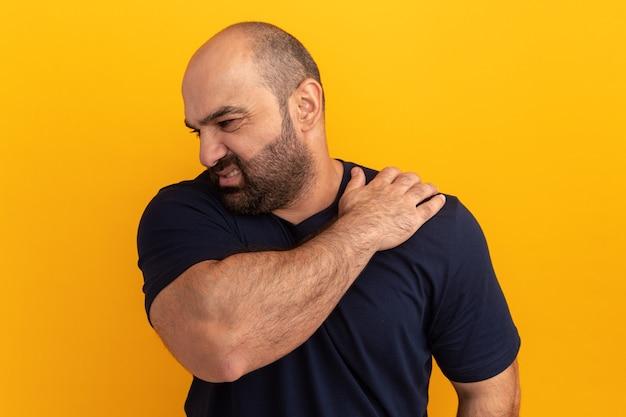 Hombre barbudo en camiseta azul marino con aspecto de malestar tocando su hombro sintiendo dolor de pie sobre la pared naranja