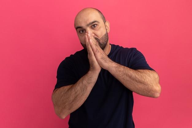 Hombre barbudo en camiseta azul marino sosteniendo las palmas juntas frente a su rostro estresado y preocupado de pie sobre la pared rosa
