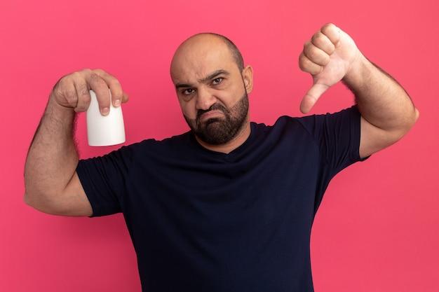 Hombre barbudo en camiseta azul marino sosteniendo una taza disgustado mostrando los pulgares hacia abajo de pie sobre la pared rosa