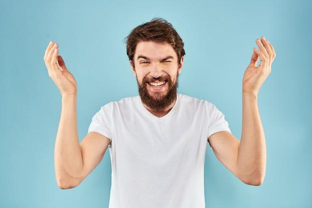 Hombre barbudo en camiseta blanca posando contra la pared azul