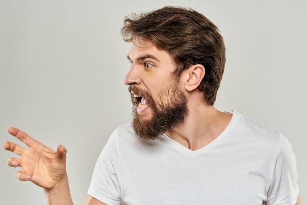 Hombre barbudo en camiseta blanca posando contra la pared gris
