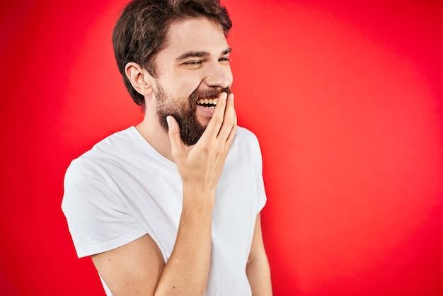 Hombre barbudo en camiseta blanca posando contra la pared roja