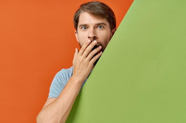Hombre barbudo en camiseta gris maqueta verde cartel fondo naranja. foto de alta calidad