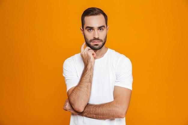 Hombre barbudo en camiseta mirando a la cámara estrictamente mientras está de pie, aislado en amarillo