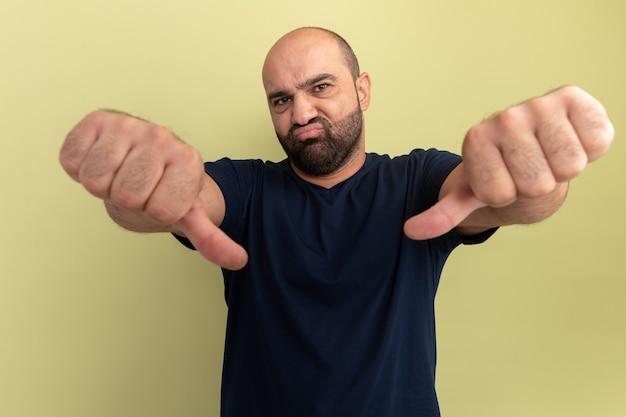 Hombre barbudo en camiseta negra disgustado mostrando los pulgares hacia abajo de pie sobre la pared verde