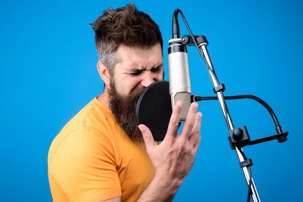 Hombre barbudo cantando en el micrófono en el estudio de grabación de música show business estudio de grabación masculino
