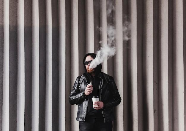 Hombre barbudo con cigarrillo electrónico al aire libre. chico elegante sosteniendo café y vaping