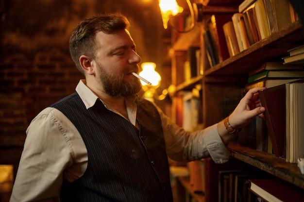 Hombre barbudo con cigarrillo toma el libro de la estantería y el rico interior de la oficina. cultura del tabaquismo, sabor específico. hábito de fumar
