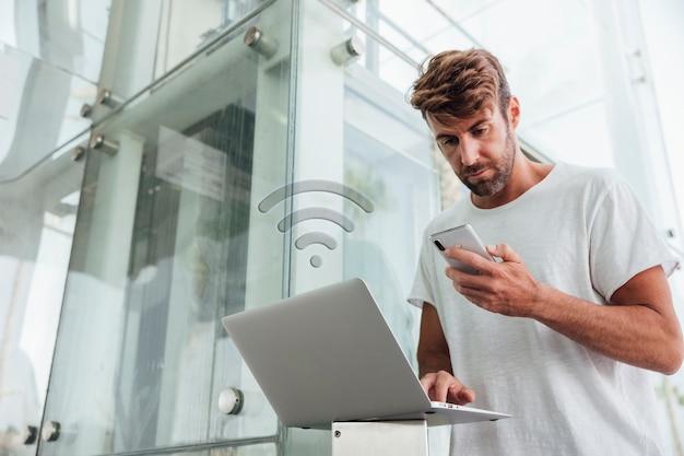 Hombre barbudo comprobando dispositivos portátiles