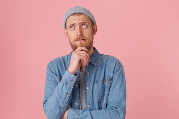 El hombre barbudo está concentrado, mantiene el puño cerca de la barbilla, intenta tomar una decisión, mira hacia arriba con una mirada pensativa y triste, se muerde el labio, duda, reflexiona sobre algo, aislado
