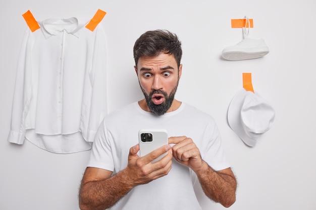Hombre barbudo conmocionado sostiene el teléfono mira fijamente la pantalla vende ropa innecesaria en línea mira fijamente los ojos con errores viste una camiseta casual aislada sobre una pared blanca lee noticias impactantes