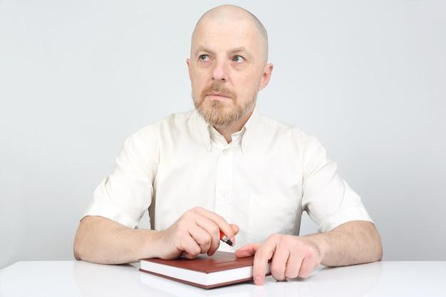 Hombre barbudo con un cuaderno y un bolígrafo en sus manos piensa