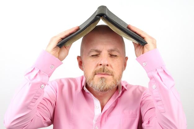 Hombre barbudo cubre su cabeza con una biblia abierta