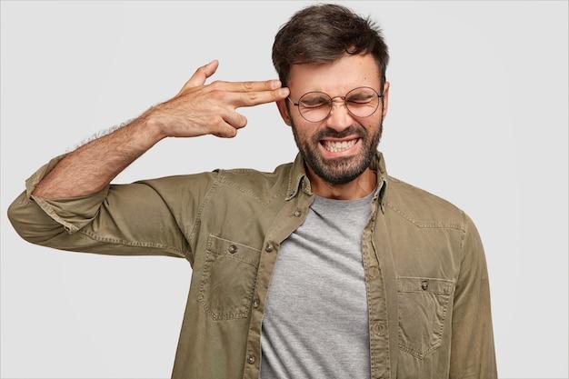 Hombre barbudo deprimido aprieta los dientes, dispara en la sien con la mano, finge suicidarse cansado de todo, posa contra la pared blanca. hombre atractivo intenta evitar todos los problemas
